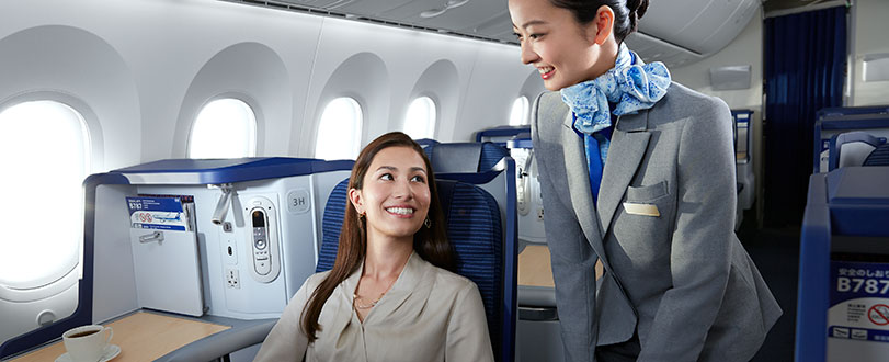 woman in business class seat with cabin crew member