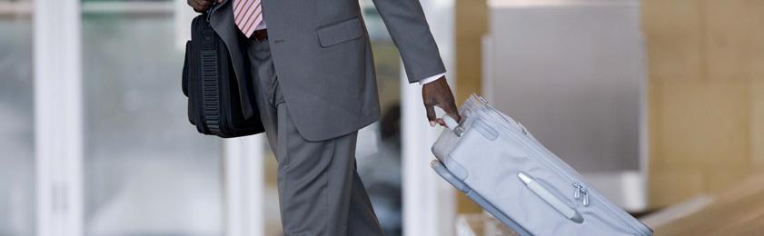 man picking up luggage from carousel